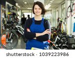 Small photo of Portrait of happy repairwoman standing near cycle in bicycle store
