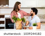 Small photo of Cute couple in love having sweet talk in cozy kitchen, bearded man, in light blue t-shirt, holding metallic tablet, beautiful long-haired woman, in stylish red shirt, standing nearby with shopping bag