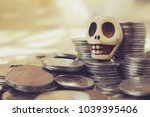 Small photo of A toy human skull on piles of coins.