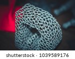 Small photo of Abstract object of a gray color printed on a 3d printer on black dark surface. Fused deposition modeling, FDM. Progressive modern additive technology. Concept of 4.0 industrial revolution