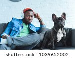 Stock photo young man in headphones listening to music and sitting by french bulldog 1039652002