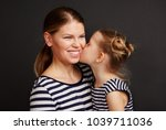 petty girl kissing her mother.... | Shutterstock . vector #1039711036