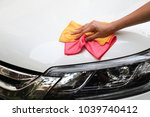 Stock photo closeup of white car cleaning with yellow and pink microfiber cloths by woman s hand 1039740412