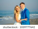 handsome groom in a chic suit and a beautiful bride in a wedding dress hug and love each other on the beach. concept of a chic and rich wedding ceremony on the beach