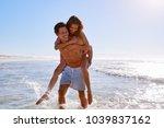 man giving woman piggyback on... | Shutterstock . vector #1039837162