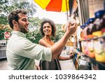 couple buying a hot dog in a... | Shutterstock . vector #1039864342