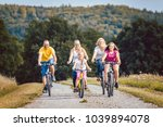 family riding their bicycles on ... | Shutterstock . vector #1039894078