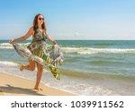 a pretty woman running along a... | Shutterstock . vector #1039911562