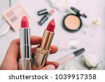 a person holds two lipsticks.... | Shutterstock . vector #1039917358