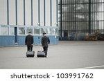 Flight crew is walking to hangar - selective focus - stock photo