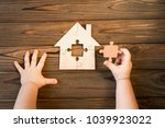 Stock photo a puzzle house in the hands of a child on a wooden background logical game housing the property 1039923022