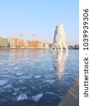 Small photo of Berlin, Germany - March 4, 2018: Iced river Spree with the popular landmark Molecule Man, Berlin Kreuzberg during a cold winter
