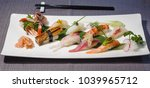Small photo of mix of different nigiri on a bamboo leaf served with daikon and radish julienne, traditional Japanese food, squid, salmon, swordfish, tuna, lobster, shrimp, prawn, amberjack, roasted eel, wasabi