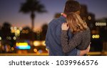 Small photo of Couple shown from behind embracing and being affectionate downtown