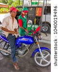 Small photo of FLORES, GUATEMALA - AUGUST 12, 2008: Service station attendant puts gasoline into motorcycle fuel tank.