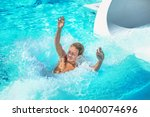 boy playing at a waterpark pool ... | Shutterstock . vector #1040074696