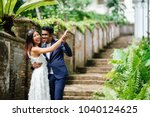 Small photo of An interracial couple (Indian man, Chinese woman) pose for wedding photographs and portraits in a park in the day. They are on old stone steps and and smiling and laughing as they take photos.