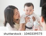 father showing milk bottle to... | Shutterstock . vector #1040339575
