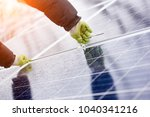 male installs solar batteries... | Shutterstock . vector #1040341216