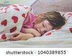 sweet kid sleeping. bed time... | Shutterstock . vector #1040389855