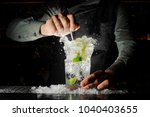 Stock photo bartender squeezing juice from fresh lime in a glass using a citrus press and splashing it out 1040403655