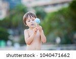 sweet little child  boy  eating ...   Shutterstock . vector #1040471662