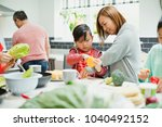 Small photo of Family are preparing vegetables for dinner in the kitchen of their home. The mother is helping the little boy prepare a yellow bell pepper.