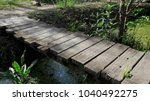 a wooden bridge over a ditch... | Shutterstock . vector #1040492275