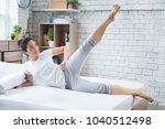 asian women exercising in bed... | Shutterstock . vector #1040512498