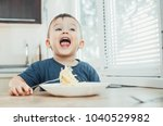 the child in the kitchen at the ... | Shutterstock . vector #1040529982