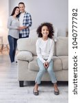 Small photo of Feeling happy. Nice alert curly-haired girl smiling and sitting on the couch and her parents standing in the background