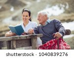 smiling nurse reading book to... | Shutterstock . vector #1040839276