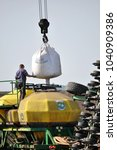 Small photo of Chortkiv - Ternopil - Ukraine - September 23, 2015. Loading bunker seeders from big bags seeds and mineral fertilizers in the agrarian enterprise Dzvin