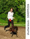 Stock photo woman walking with an american stafford in the park 104095226