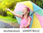kid playing out in the rain.... | Shutterstock . vector #1040978212