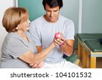 Young therapist giving muscle training for elbow joint at clinic - stock photo