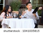 Small photo of Interracial couple on a date paying for a restaurant tab with a waitress. They are in an outdoor cafe handling the payment bill and server tip or gratuity.