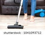 young woman vacuum cleaning the ... | Shutterstock . vector #1041093712