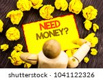 Small photo of Writing text showing Need Money Question. Business photo showcasing Economic Finance Crisis, Cash Loan Needed written Sticky Note Holding By Sculpture the wooden background
