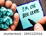 Small photo of Announcement text showing I m am On Sick Leave. Business concept for Vacation Holiday Absent Out Of Office Sickness Fever written Notebook Book Man Writing Holding Pen wooden background.