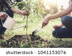 young couple planting the tree... | Shutterstock . vector #1041153076