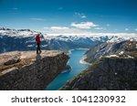 hiker woman standing on a cliff ... | Shutterstock . vector #1041230932