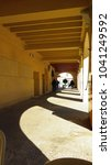 Small photo of People walking in shade through arched passage in Almeria, Spain