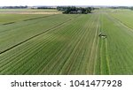 Aerial bird view photo farmer cutting grass meadow and typical farm in background flight over the grass field showing farmer in tractor cutting the fresh green grass moving over agricultural vehicle - stock photo