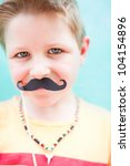 Cute boy holding mustache party accessory - stock photo
