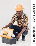 African American construction worker in helmet takes out tools from yellow plastic tool box - stock photo