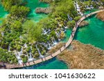Tourists on the wooden park pathways enjoying the view of emerald lakes, cascades and crystal clear water, Plitvice Lakes National Park, Croatia - stock photo