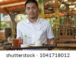 male asian waitercarrying food... | Shutterstock . vector #1041718012