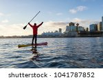 Stock photo adventurous man is paddle boarding near downtown city during a vibrant winter sunrise taken in 1041787852