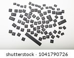 Small photo of Loose alphanumeric covers for the keys on a computer keyboard in a random jumble on a white or light silver background viewed from overhead centered in the screen with surrounding copy space